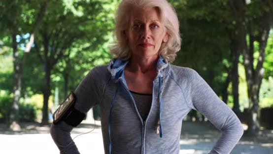 Thumbnail for Healthy senior woman jogger standing in the park with hands on her hips