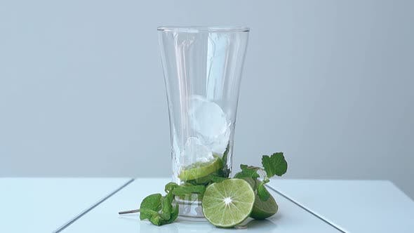 Glass with Lime and Ice Cubes Stands on White Table at Wall