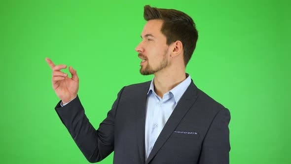 Thumbnail for A Young Handsome Businessman Talks To the Camera and Points at Objects Falling Around Him