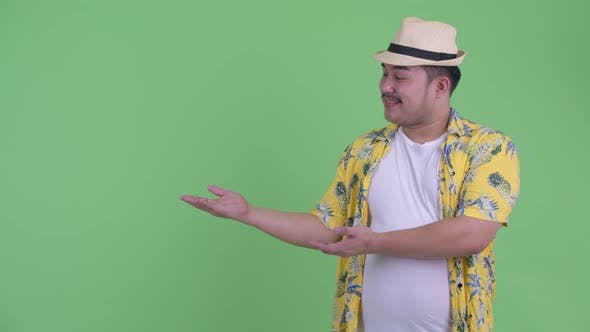 Cover Image for Happy Young Overweight Asian Tourist Man Showing Something and Giving Thumbs Up