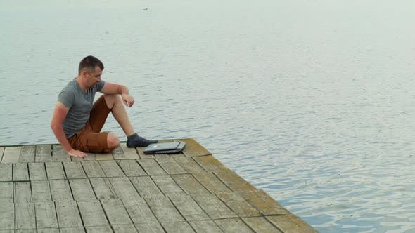 Man on the pier working on a laptop