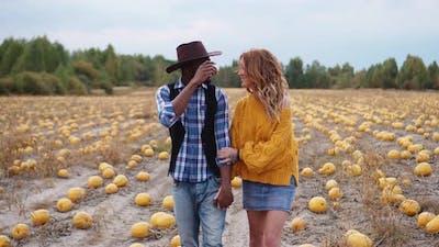 Couple Walking on Pumpkin Field Holding Hands