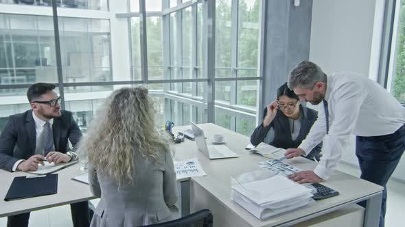 Cover Image for Executive Manager Discussing Document with Colleagues