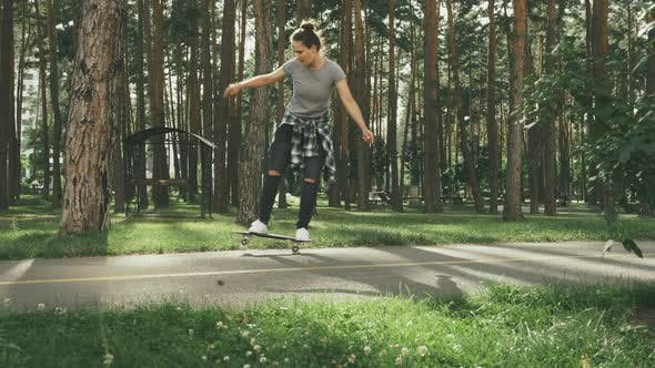 Thumbnail for Girl falls off a skateboard. Young female learning to skating on skateboard outdoors.