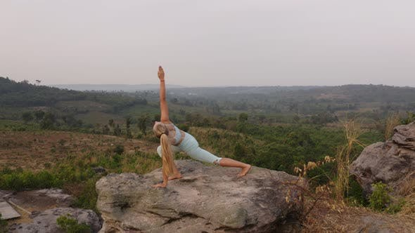 Thumbnail for Aerial Shot of Lady in Downward Dog Yoga Pose with a View From the Top of the Mountain