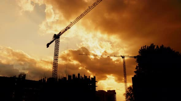 Cover Image for Silhouette of Tower Cranes Working on Construction Site Residential Golden Hour, Warm Cloudy Sky