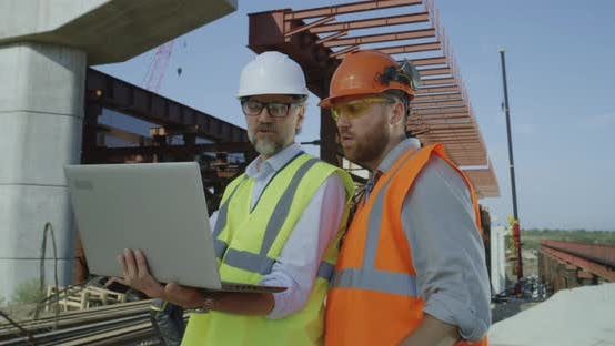 Thumbnail for Male Contractors Examining Draft on Laptop