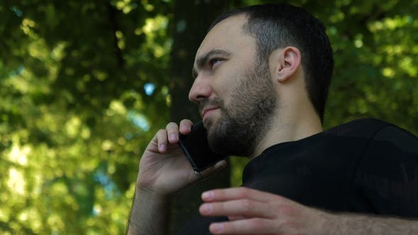 Cover Image for Serious guy talking on phone in the park.