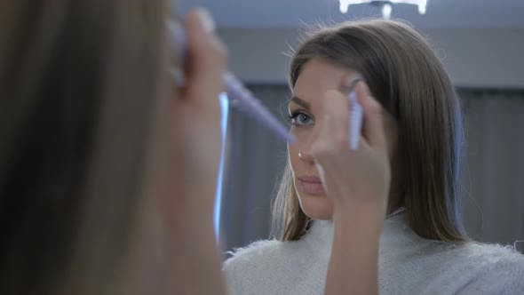 Thumbnail for Young Woman Putting Make Up on Face in Mirror