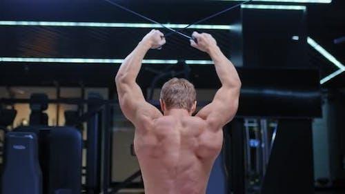 Athlet, ein Bodybuilder, streckt die Gurte hinter dem Kopf im Simulator, Züge