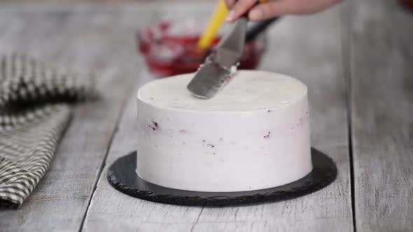 Cover Image for A confectioner prepares a cream cake, Dessert on a white table in the kitchen
