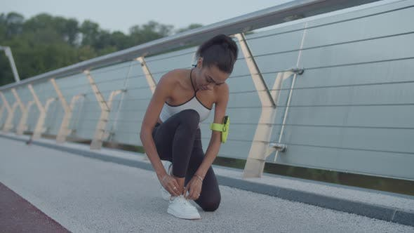 Thumbnail for Athlete Woman Tying Running Shoes During Jog at Dawn