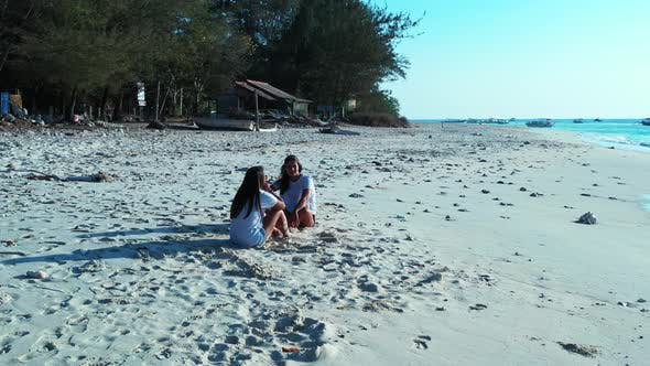 Beautiful beauty models on holiday spending quality time at the beach on paradise white sand