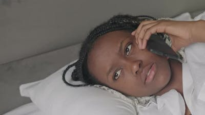 African American Woman Talking on Phone in Bed