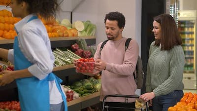 Young Couple Choosing Vegetables in Supermarket