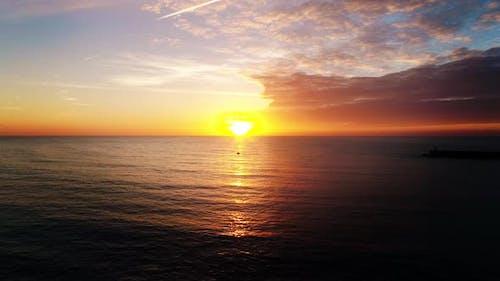 Aerial Shot of the Sun Setting Over the Ocean Horizon