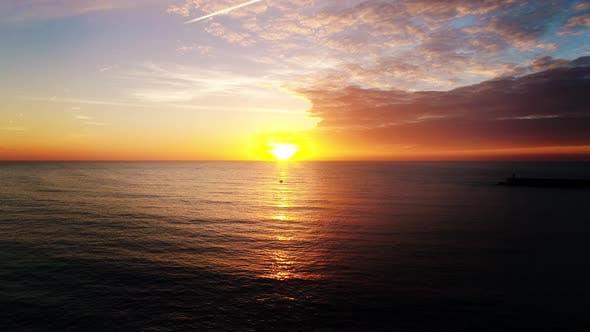 Thumbnail for Aerial Shot of the Sun Setting Over the Ocean Horizon