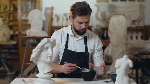 Thumbnail for Young Male Master with Beard Preparing Mixture in Special Vassel for His Handmade Sculpture