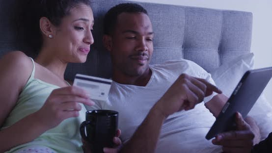 Thumbnail for Happy Black and Hispanic couple making online purchase with tablet computer browsing the internet in