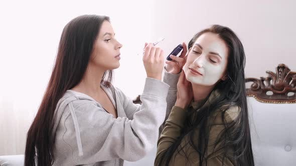 Thumbnail for The Woman Is Applying a Face Mask on Her Friend's Face