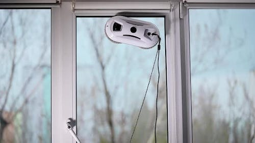 The Automatic Robot Assistant Washes the Glass of the Window