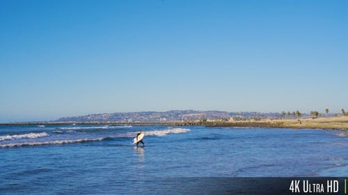 4K Surfer Guy with Surfboard Walking out of Water Towards Beach
