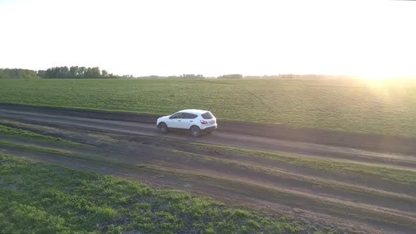 Thumbnail for Car Drives Along Ground Road Past Fields at Bright Sunset