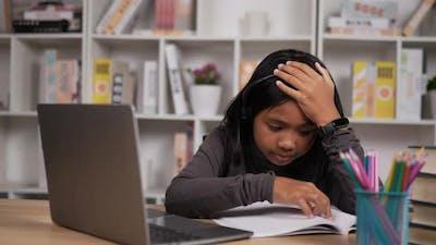 Tired girl learning online via laptop
