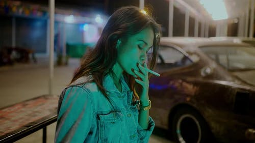 A Girl Smokes in Front of a Rusty Classic Car While Typing a Message Late at Night