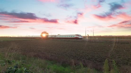 High speed white and red train is passing against a beautiful sunset sky