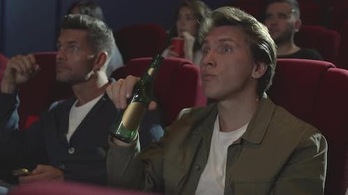 People Watching Exciting Thriller in Cinema