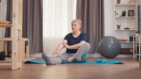 Old Woman Stretching on Yoga Mat