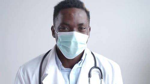 African Black Male Doctor Wears Face Mask Looking at Camera Close Up Portrait