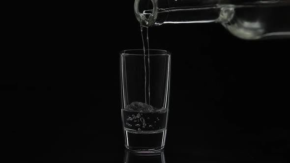 Thumbnail for Pouring Up Shot of Vodka From a Bottle Into Glass. Black Background