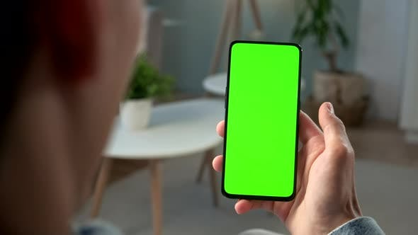 Thumbnail for Back View of Brunette Man Holding Chroma Key Green Screen Smartphone Watching Content Without