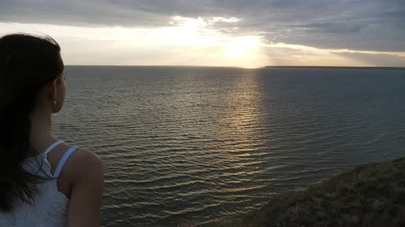 Thumbnail for Beautiful Girl in a Sleeveless Blouse Looking at Sunset at Black Sea in Slo-mo