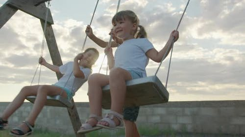 Children of Different Age and Gender Ride on a Swing. Happy Childhood Concept.