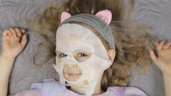 Teen Girl Applying Moisturizing Face Mask, Child Kid Take Care of Skin with Cosmetic Facial Mask