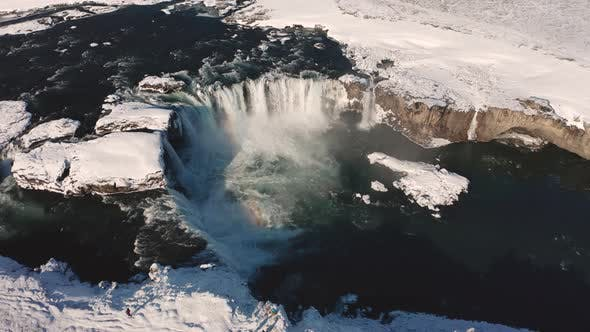 Aerial View of Godafoss Waterfall with Snowy Shore and Ice, Iceland, Winter 2019