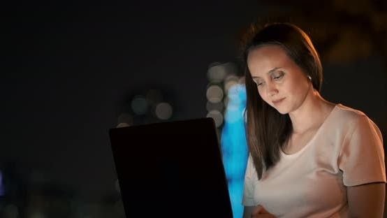 Thumbnail for Young Female Student with Laptop at Night in Town Typing Text