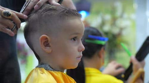 Children's Haircut in the Salon at the Time of the Coronavirus Epidemic. Little Boy Gets a Haircut