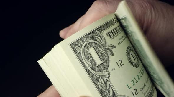 Person flipping through bundle of 1 dollar bills