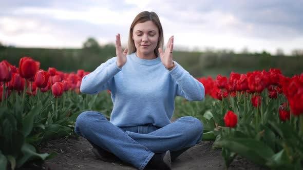 Ruhige Frau entspannt meditiert allein im Tulpenfeld