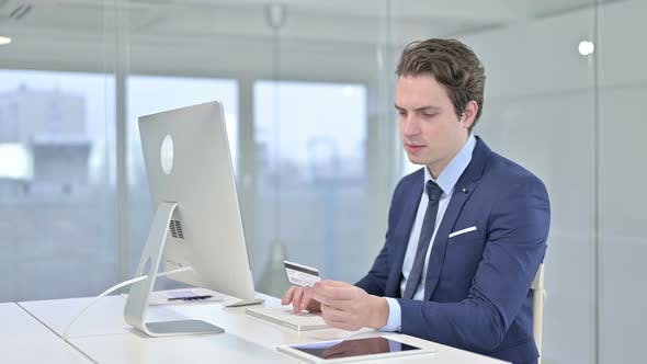 Thumbnail for Focused Young Businessman Making Online Payment on Desk Top