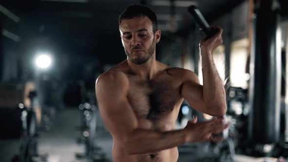 A Muscular Sportsman is Doing Exercise in the Gym