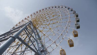 Big Ferris Wheel Rotates at Amusement Park Carnival Ride Over Clean Blue Sky
