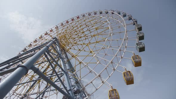Thumbnail for Big Ferris Wheel Rotates at Amusement Park Carnival Ride Over Clean Blue Sky