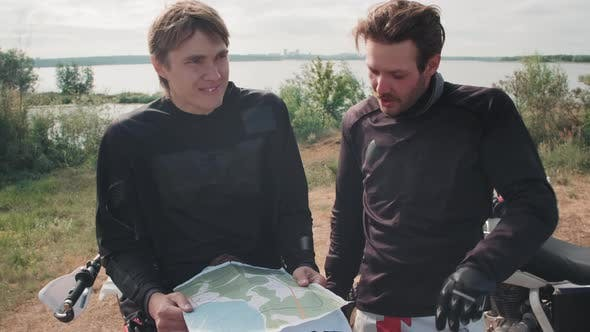 Male Motorcyclists Looking at Map and Planning Route