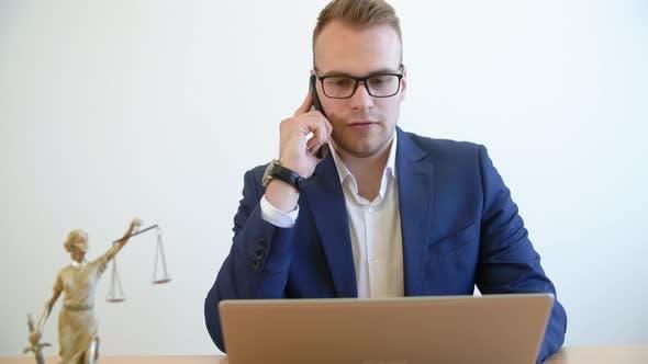 Thumbnail for Young Lawyer spricht Handy und Arbeiten am Laptop am Tisch in der Anwaltskanzlei