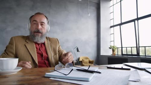 Man Drinking Tea and Enjoying Audio Book